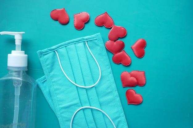 Chirurgische maskers met hartvorm en handdesinfecterend middel op kleurenachtergrond