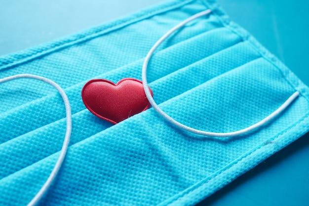 Chirurgische maskers met hartvorm en handdesinfecterend middel op kleuroppervlak