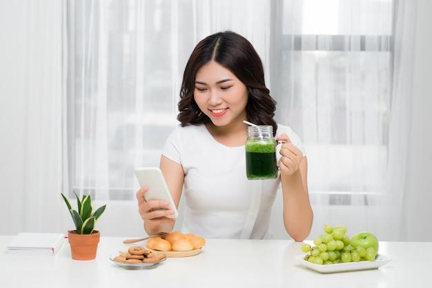 Chit-chat met haar vrienden. vrouw praat op haar mobiel tijdens het ontbijt bij haar thuis
