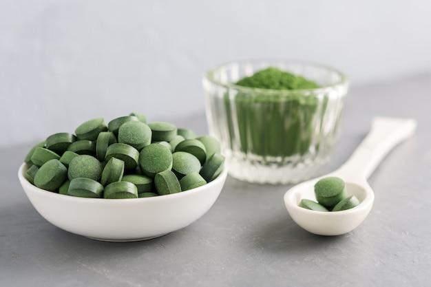 Chlorella of spirulina in de vorm van tabletten en poeder op een grijze betonnen achtergrond.