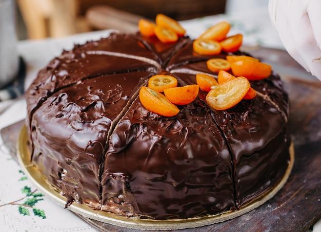 Chococake die in plakjes wordt gesneden lekker heerlijk rond geheel ontwerpen met kumquats noten