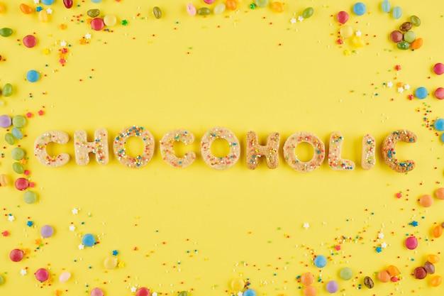 Chocoholic woord gemaakt van zoete koekjes versierd met kleurrijke hagelslag en chocoladesuikergoed rond