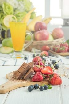 Chocolade, aardbei, bosbes en ijsblokjes op houten plaat