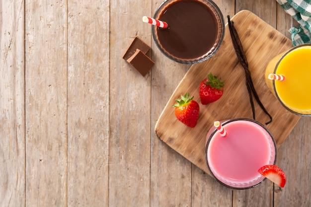 Chocolade, aardbei en vanille milkshakes op rustieke houten tafel