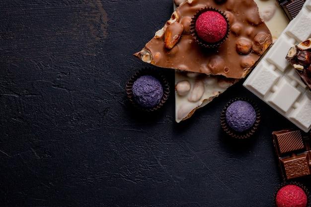 Chocolade achtergrond. chocola. assortiment fijne chocolaatjes in witte, donkere en melkchocolade. praline chocoladesnoepjes.