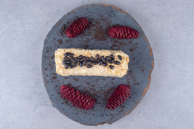 Chocolade bedekte cake en rode dennenappels op een houten bord op marmeren tafel.