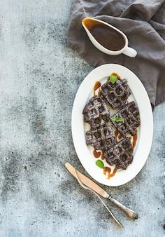 Chocolade belgische wafels met gezouten karamelsaus en munt op witte keramische serveerschaal