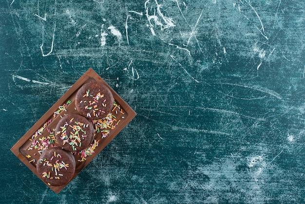 Chocolade biscuit sandwiches met hagelslag op een houten bord.