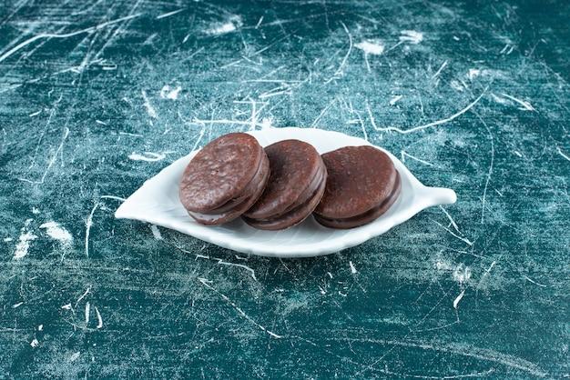 Chocolade biscuit sandwiches op witte plaat.