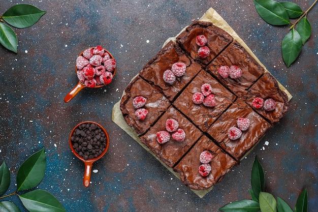Chocolade brownie cake dessert plakjes met frambozen en kruiden, bovenaanzicht