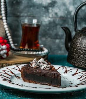 Chocolade brownie gegarneerd met room en geraspte chocolade