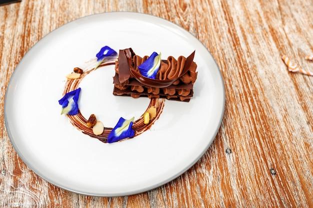 Chocolade brownie versierd met blauwe bloemen op een bord