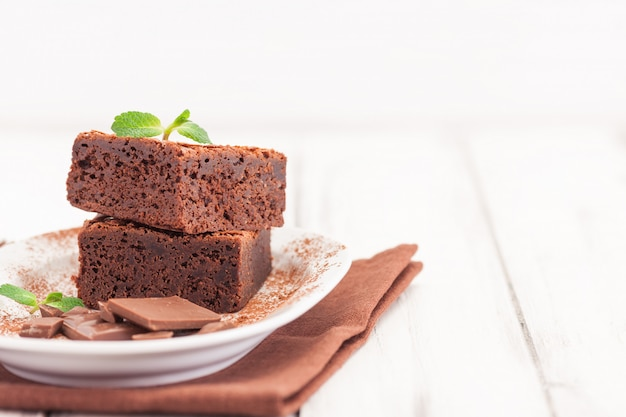 Chocolade brownie vierkante stukken in stapel op witte plaat versierd met muntblaadjes