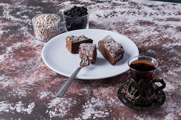 Chocolade brownies geserveerd met een glas thee.