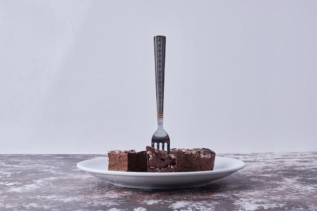 Chocolade brownies in een witte plaat met een vork erop op een grijze achtergrond