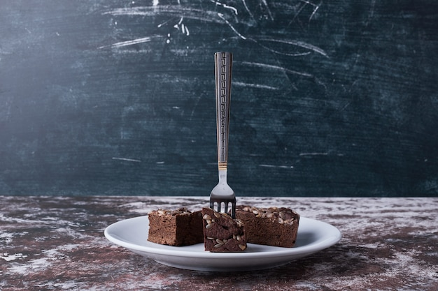 Chocolade brownies in een witte plaat met een vork erop.