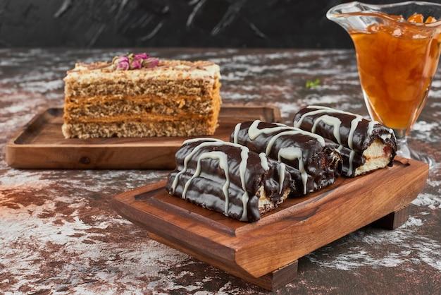 Chocolade brownies met een plakje cake op een houten bord.