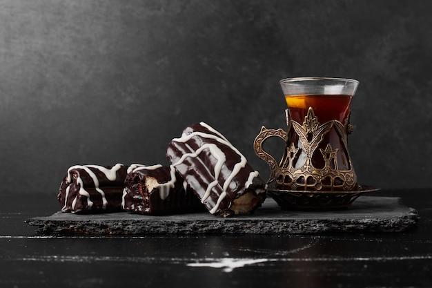 Chocolade brownies op een stenen schotel met een glas thee.