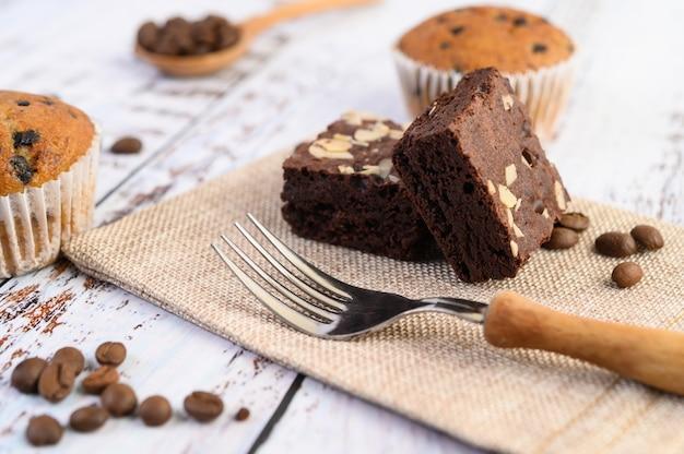 Chocolade brownies op zak en koffiebonen, vork op een houten tafel.