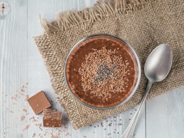 Chocolade chia pudding in glas en chocolade blokjes segment met rustieke servet op grijze houten tafel.