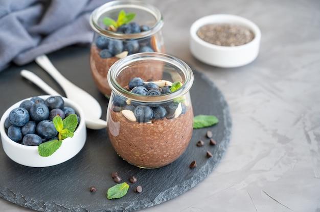 Chocolade chia pudding met bosbessen, amandelen en munt bovenop in een glazen pot op een grijze betonnen ondergrond. gezond eten. ruimte kopiëren.