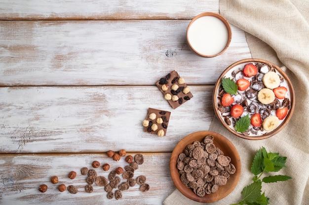 Chocolade cornflakes met melk en aardbei in houten kom o