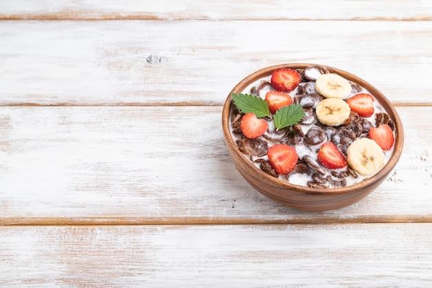Chocolade cornflakes met melk en aardbei in houten kom