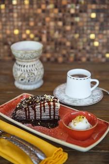 Chocolade crêpe cake met vanille-ijs geserveerd met thee