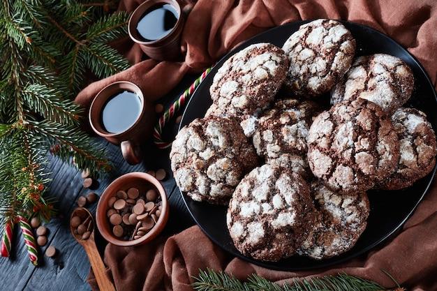 Chocolade crinkle kerstkoekjes op een plaat op een zwarte houten tafel met dennenboom, zuurstokken, bruine doek en kopjes koffie, rustieke stijl, horizontale weergave van bovenaf