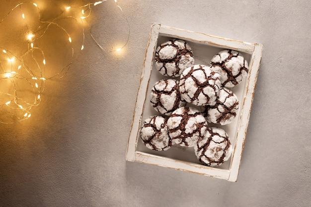 Chocolade crinkle koekjes in houten kist met kerstverlichting feestelijke zelfgemaakte zoetigheden