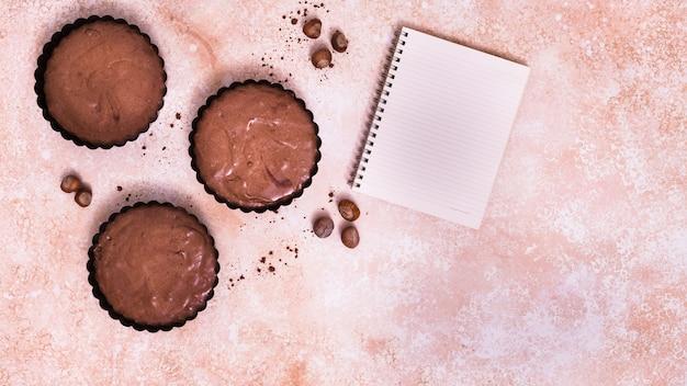 Chocolade cupcake; hazelnoot en spiraalvormige blocnote op gestructureerde achtergrond