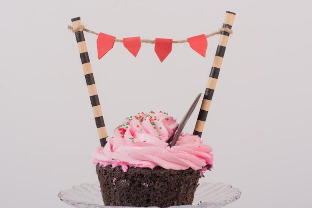 Chocolade cupcake met glazuur en sprinklers op glas.
