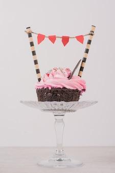 Chocolade cupcake met glazuur en sproeiers op glas.