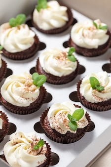 Chocolade cupcakes met kaascrème en muntblaadjes in verzenddoos
