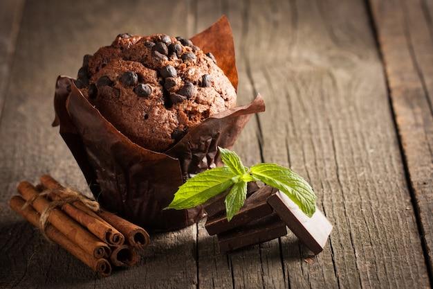 Chocolade donkere gekookte muffin met munt op een houten tafel met kaneel, anijs, chocolade.