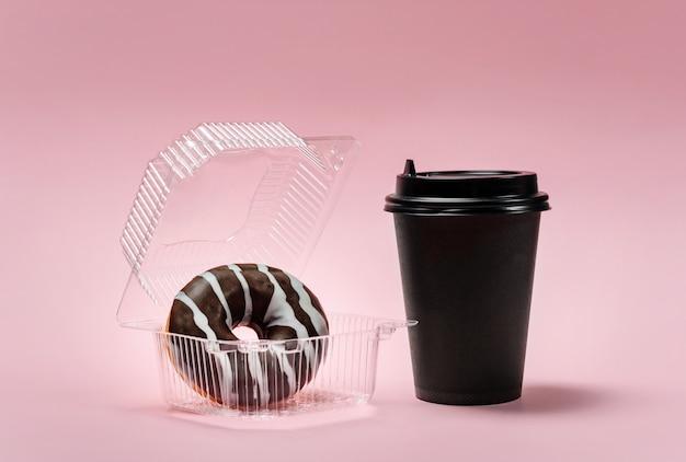Chocolade donut in een plastic bakje en een papieren blikje voor koffie of thee