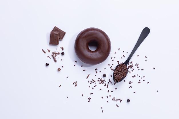 Chocolade donuts en chocoladeschilfers op witte achtergrond. bovenaanzicht.