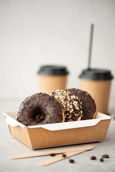 Chocolade donuts met glazuur in een ambachtelijke doos en zwarte koffie in kopjes op een witte tafel