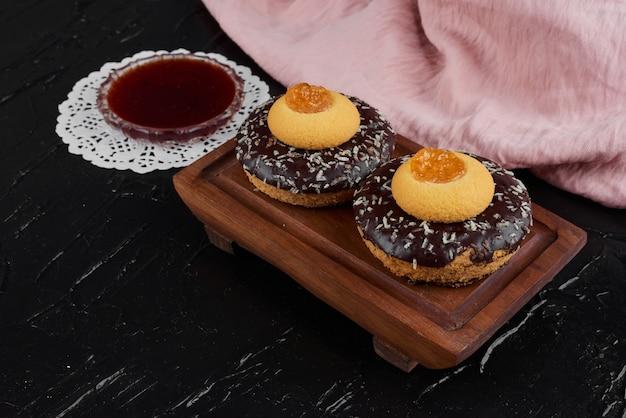 Chocolade donuts op een houten bord met boterkoekjes.