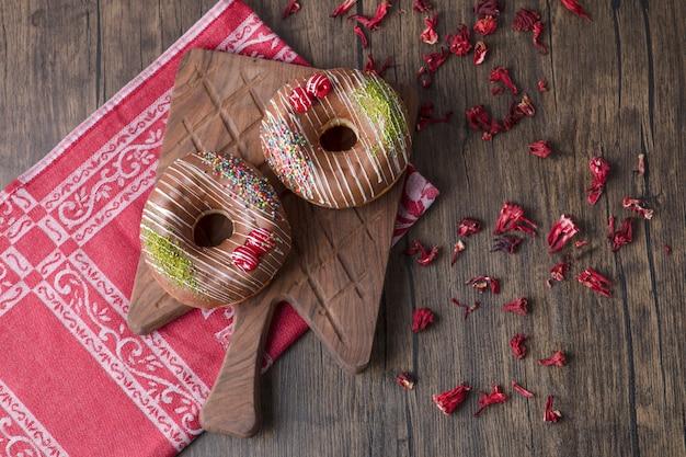 Chocolade donuts op een houten bord met gedroogde rozenblaadjes.