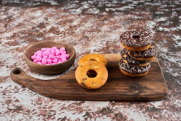 Chocolade donuts op een houten bord met roze snoepjes.