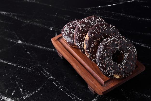 Chocolade donuts op een houten schotel.