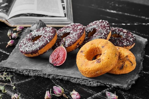 Chocolade donuts op een stenen schotel.