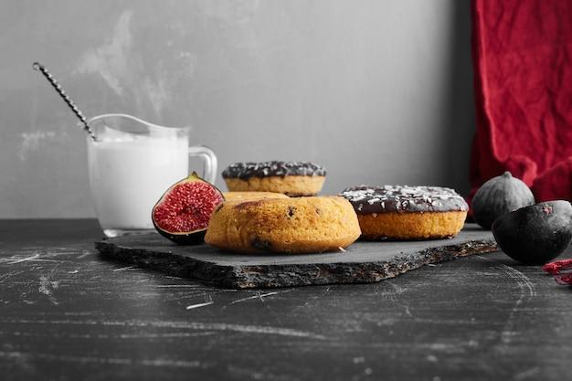 Chocolade donuts op een zwarte ondergrond op een stenen bord.