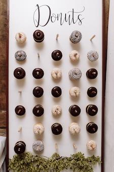 Chocolade donuts voor gasten. feestelijk concept. snoepjes op een trouwdag. bruiloft donuts