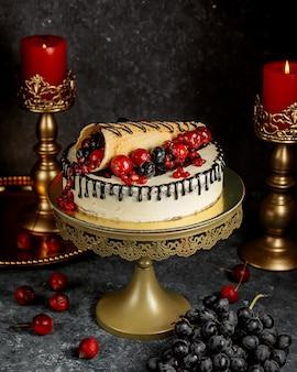 Chocolade druipende cake gegarneerd met verpakte wafel met bessen