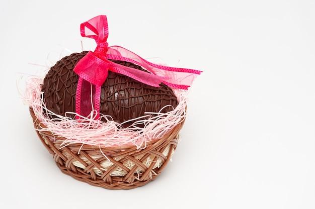 Chocolade-ei in rieten mand met mooie rode geïsoleerde lintboog