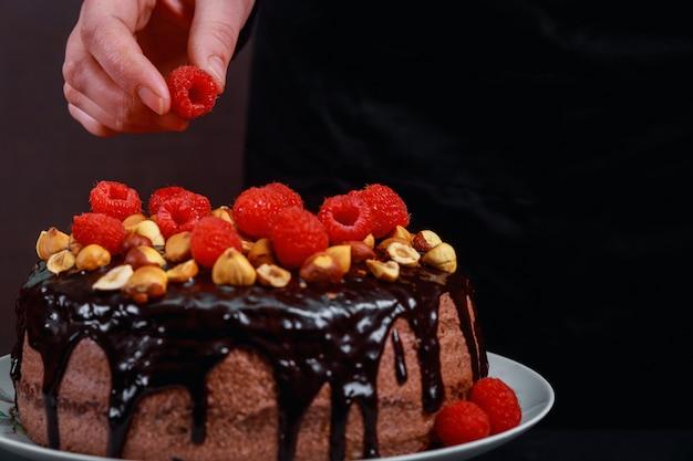 Chocolade eigengemaakte cake die met frambozen door mannelijke handen op een grijze achtergrond wordt verfraaid.