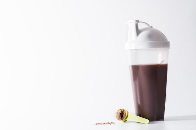 Chocolade-eiwitshake op witte achtergrond copyspace wordt geïsoleerd die