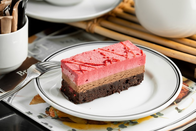 Chocolade en aardbeien cheesecake plaat gegarneerd met aardbeiensiroop